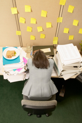 78747047_Overwhelmed_Woman_with_Head_Resting_on_Her_Desk