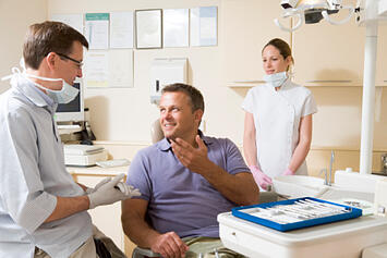84469771_Dentist_and_assistant_in_exam_room_with_man_in_chair_smiling