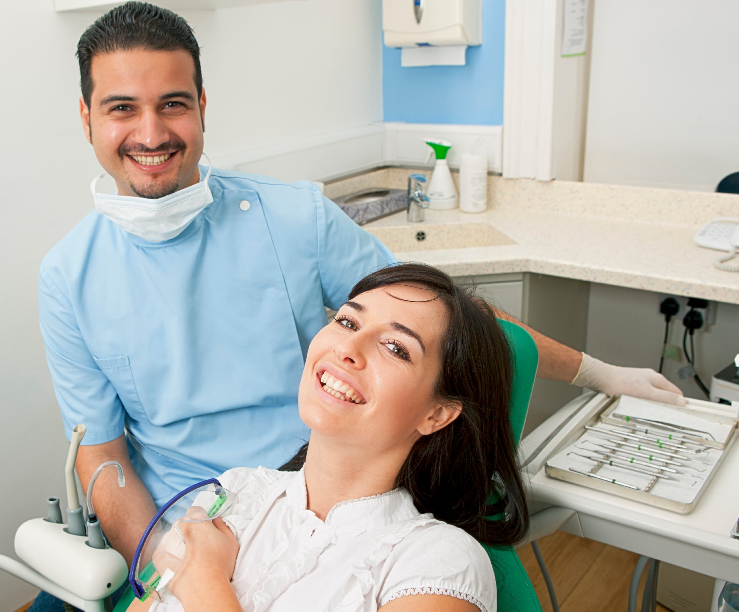 smiling woman and dentist going over dental insurance coverage
