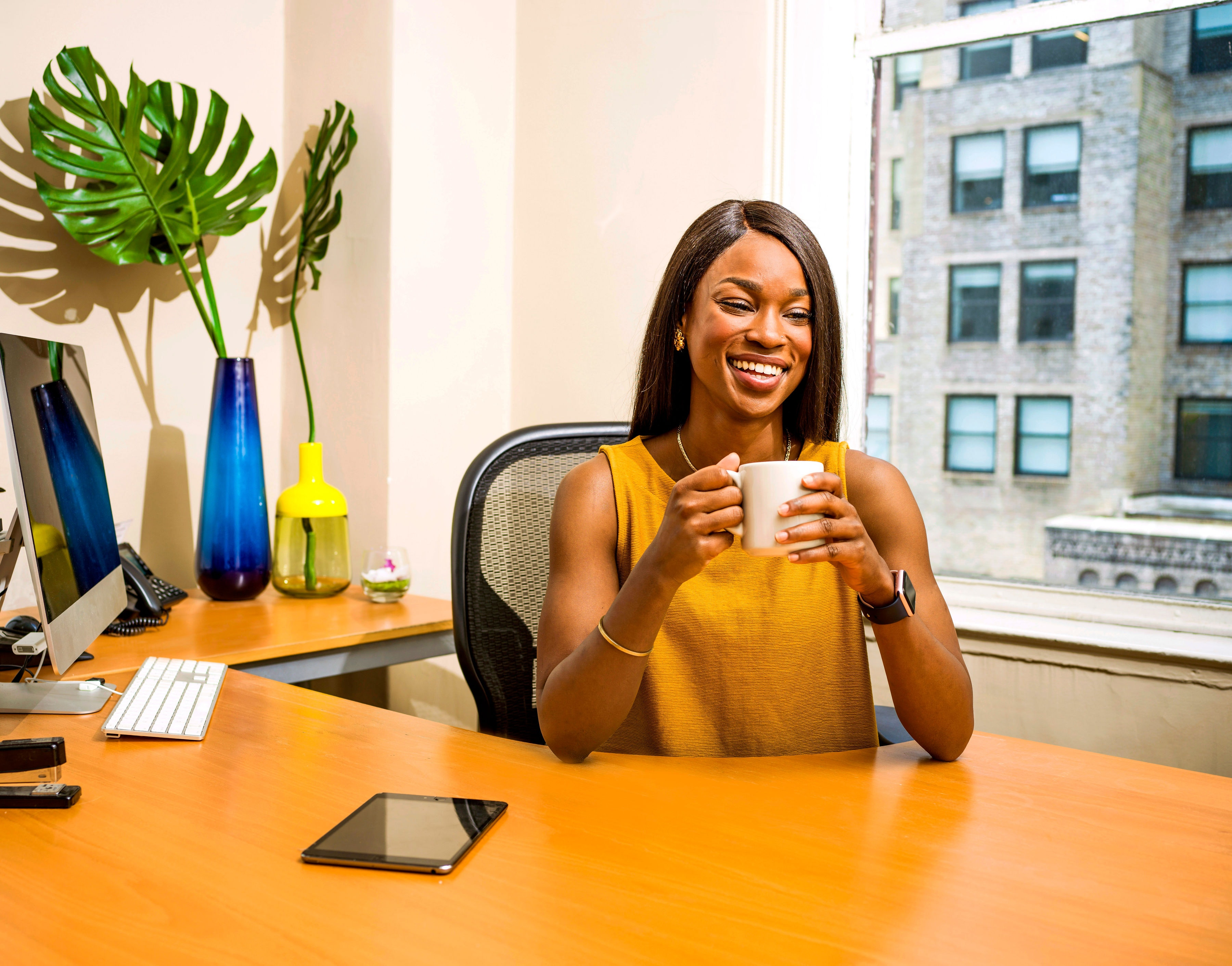 woman-holding-white-ceramic-mug-at-desk-2422287