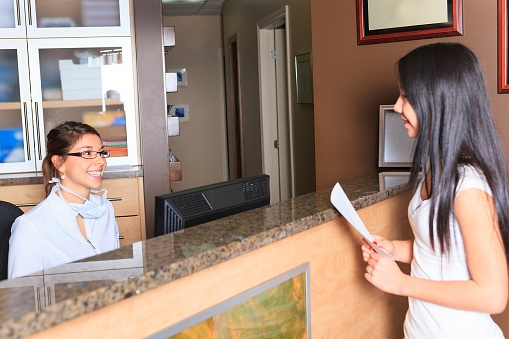 girl talking to front desk in a dental office