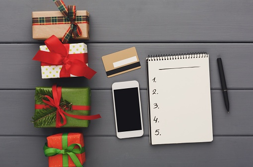 873825022 Preparing gifts for christmas, shopping online, wood background, top view..jpg