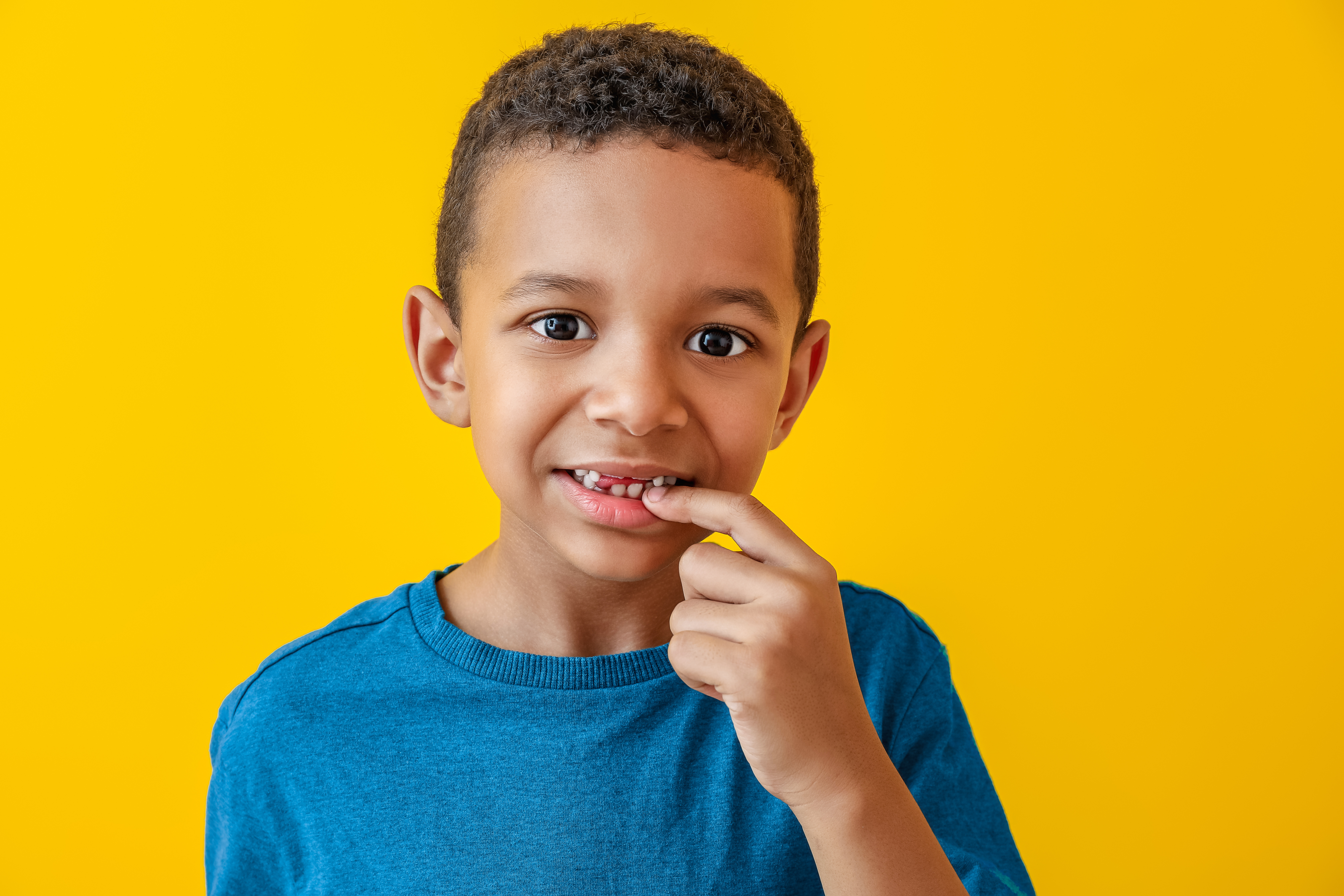 Smiling child pointing to his teeth before his back to school dental checkup
