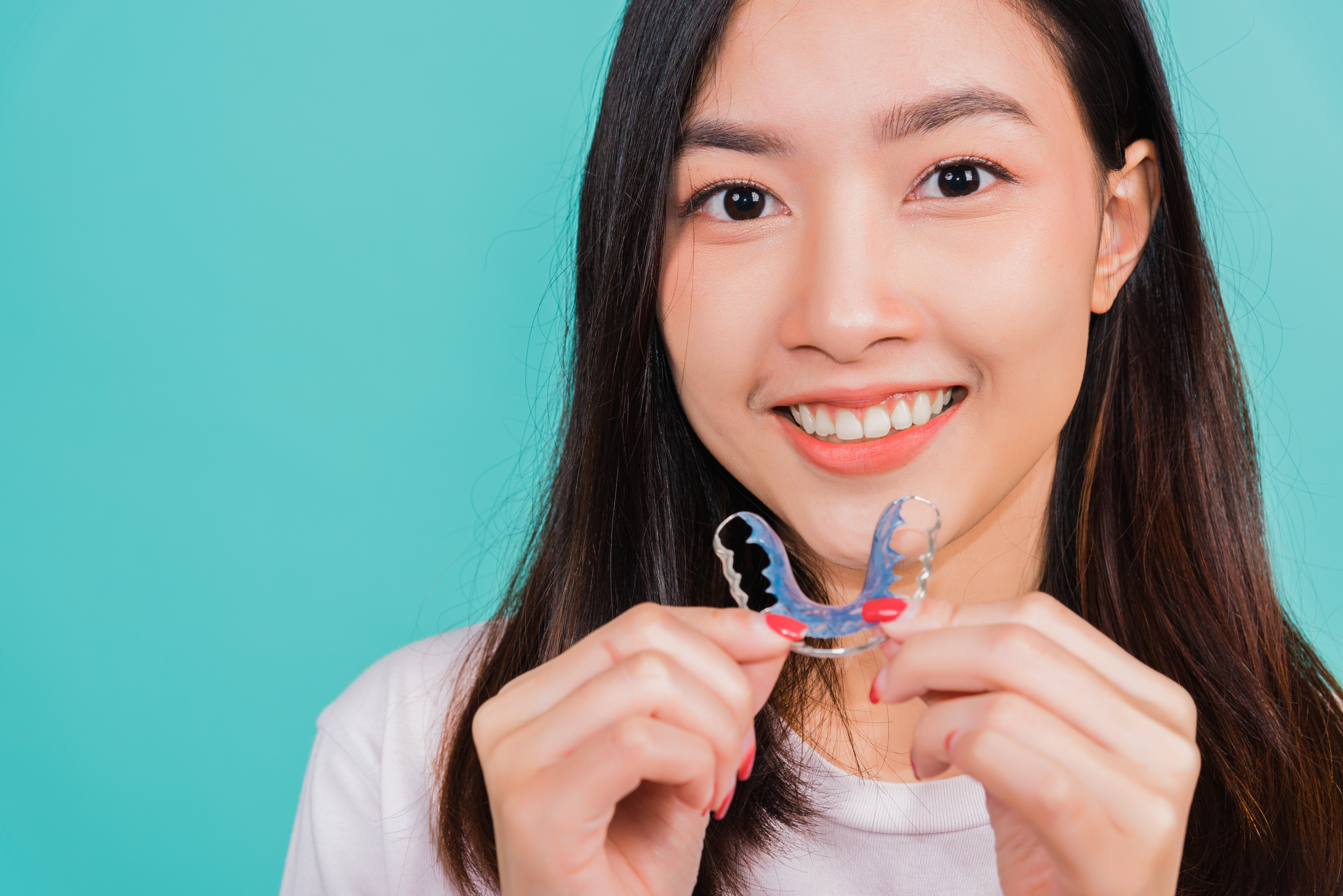 Woman smiling while holding retainer
