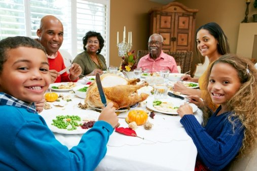 Family smiling during Thanksgiving and protecting their oral health