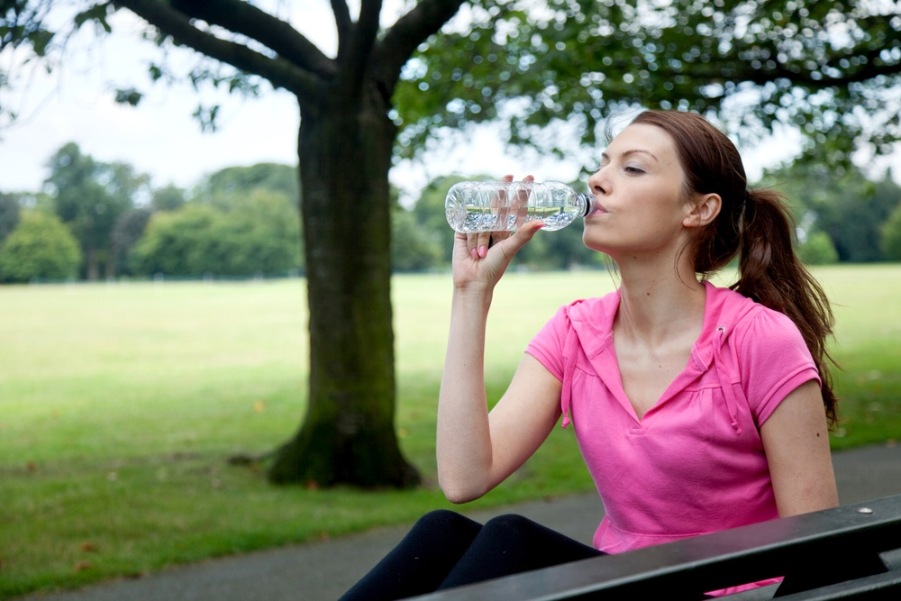 sporty woman resting on a bench drinking water