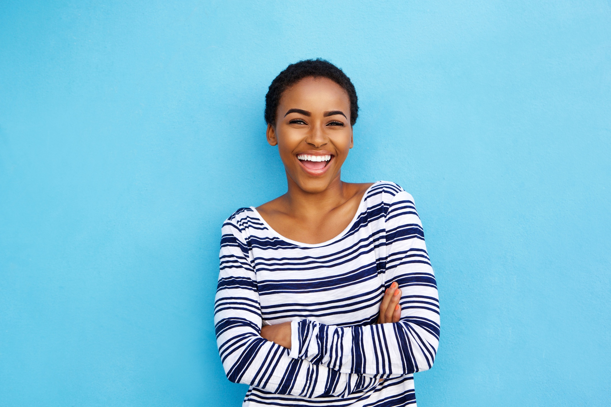 ThinkstockPhotos-857924506 Happy young black woman laughing against blue wall