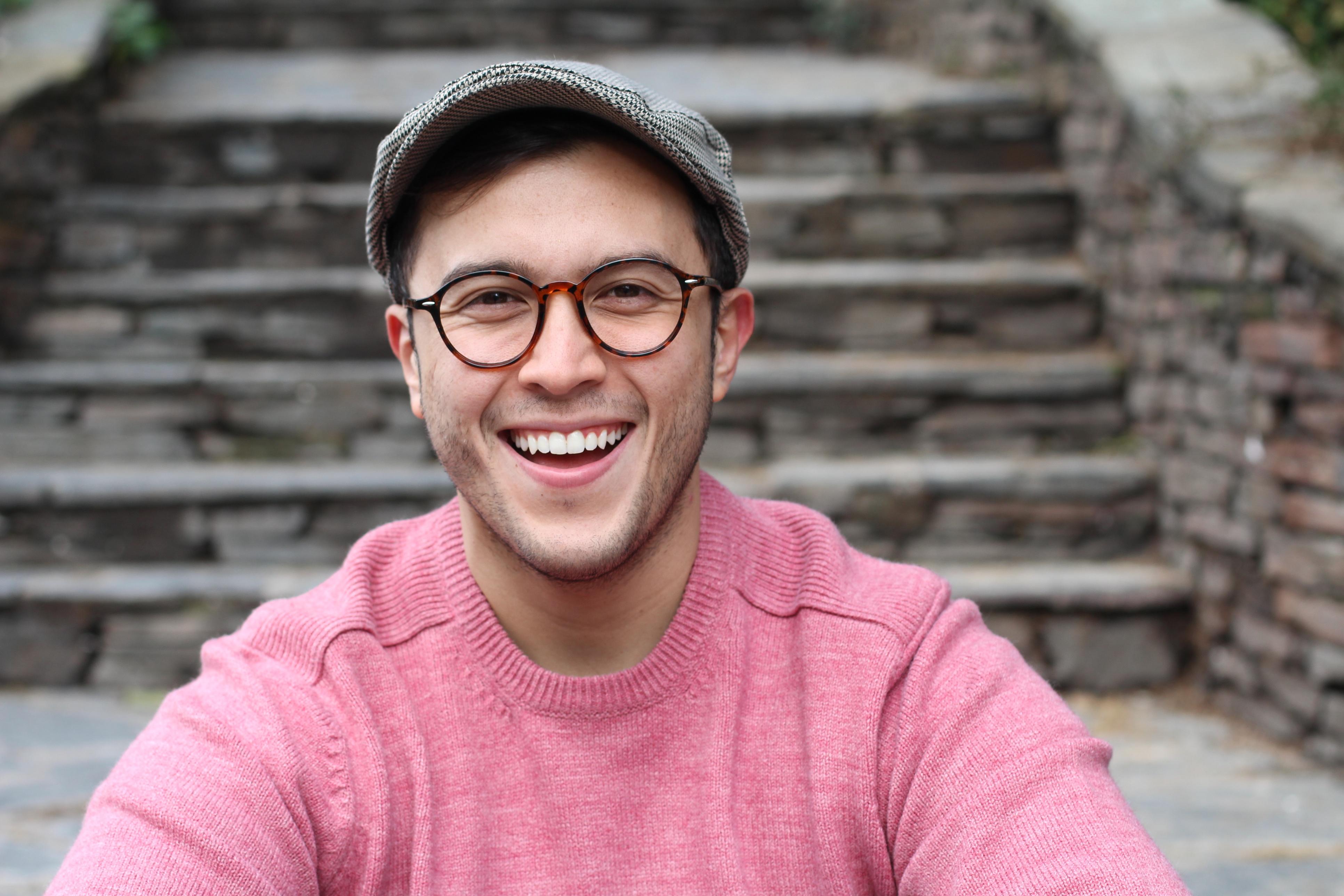 ThinkstockPhotos-937370098 Hip man smiling wearing eyeglasses and hat