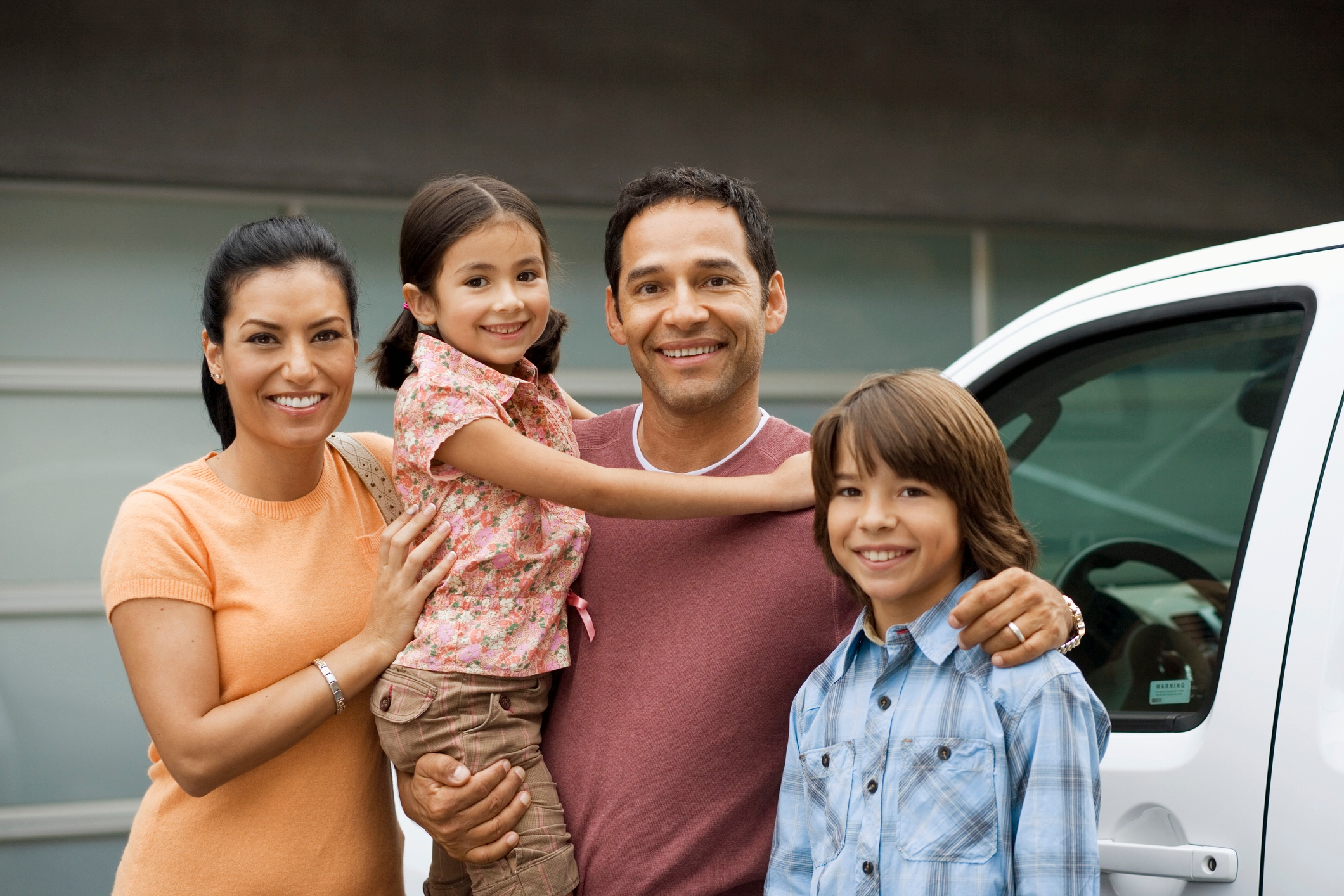 ThinkstockPhotos-200488800-001 Family standing outside house next to car