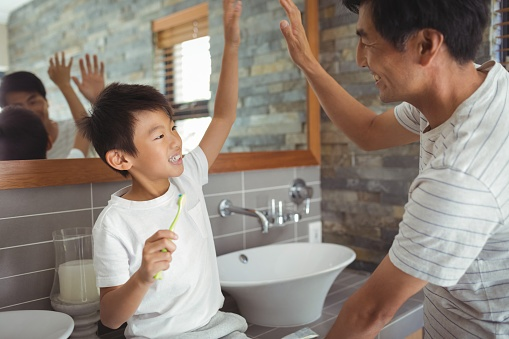 ThinkstockPhotos-800845800 Father and son giving high five to each other in bathroom.jpg
