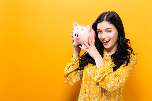 ThinkstockPhotos-848721114  Young woman with a piggy bank