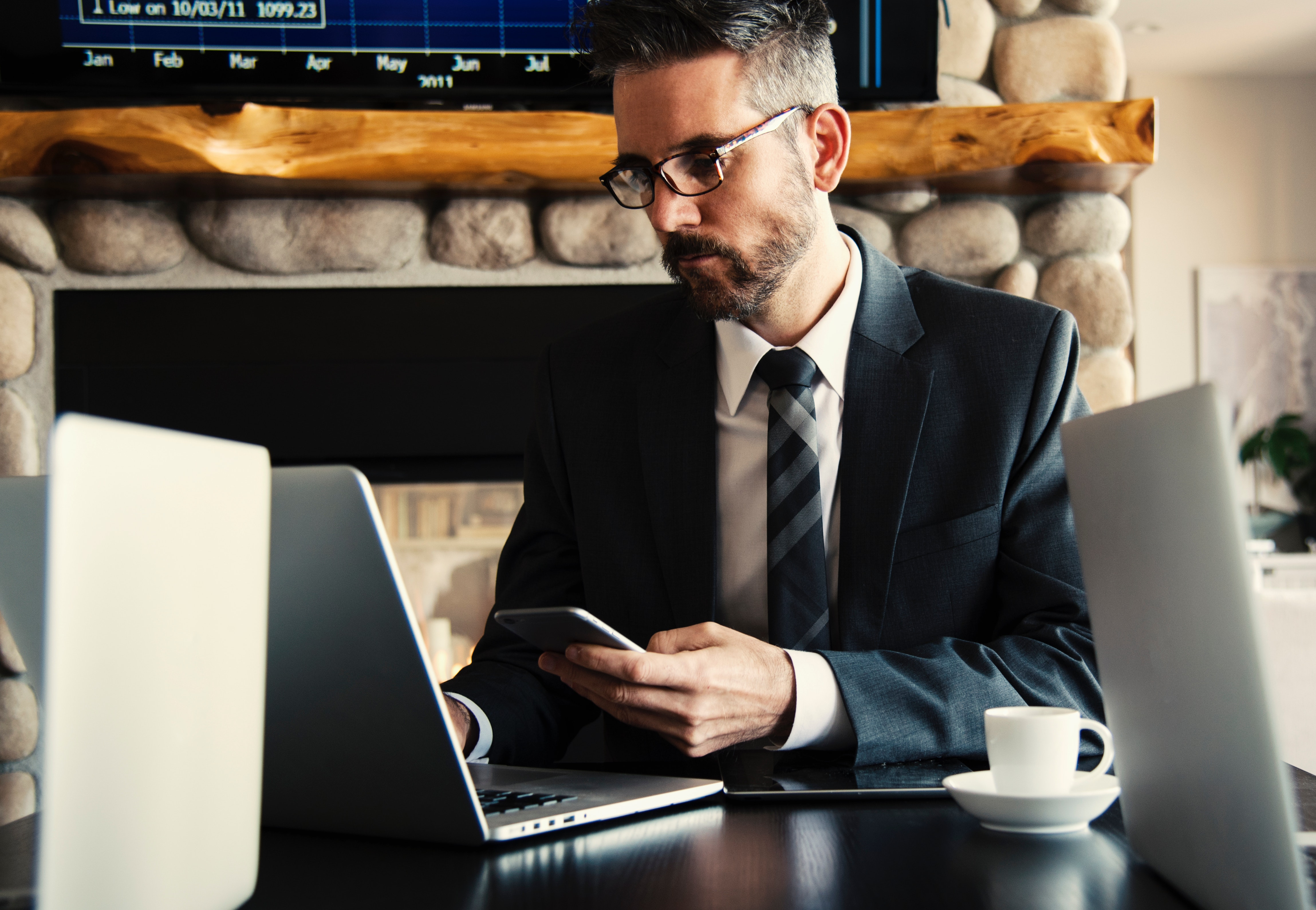Broker holding a smartphone and looking at laptop