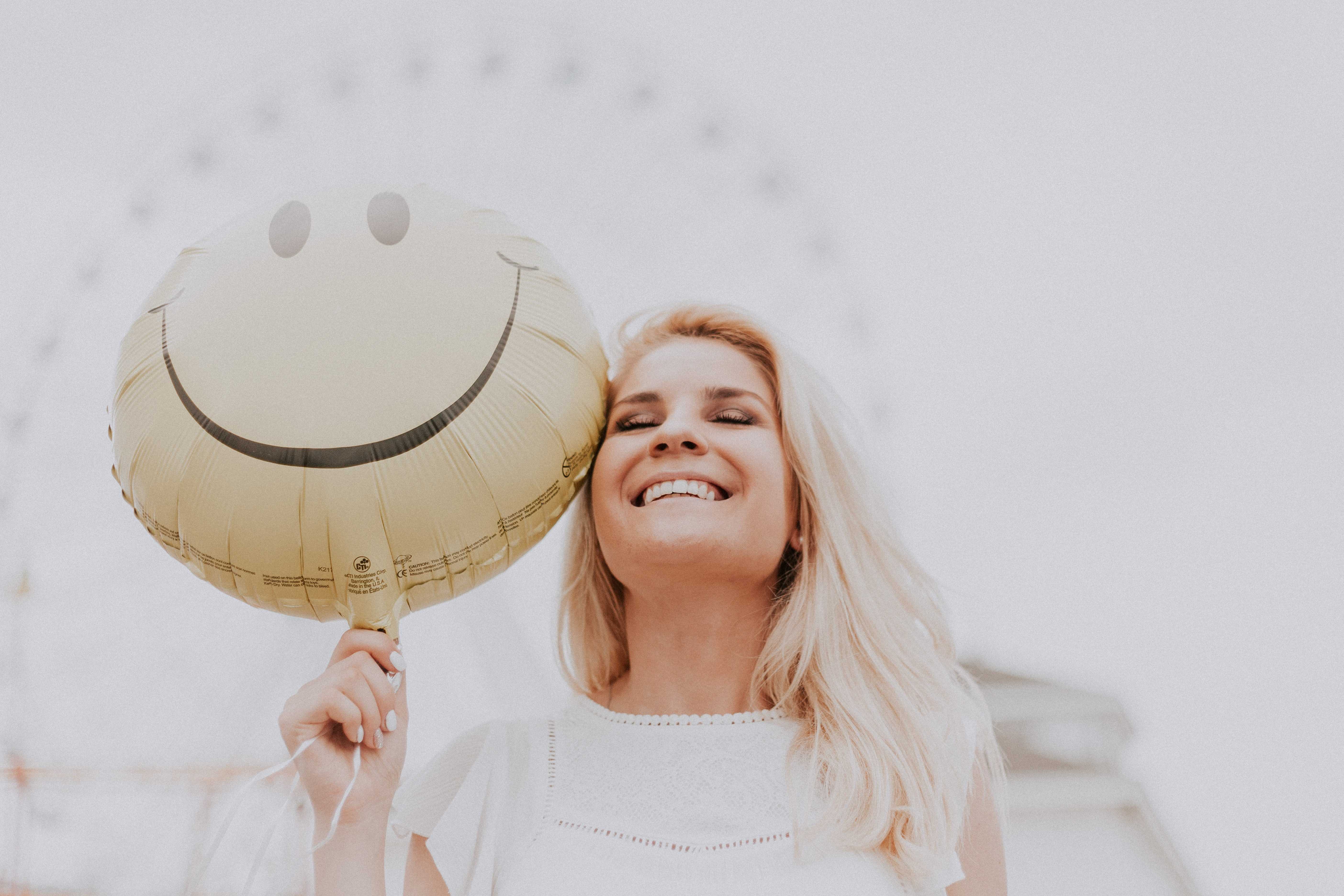 Girl with blonde hair smiling and holding a smiley face balloon
