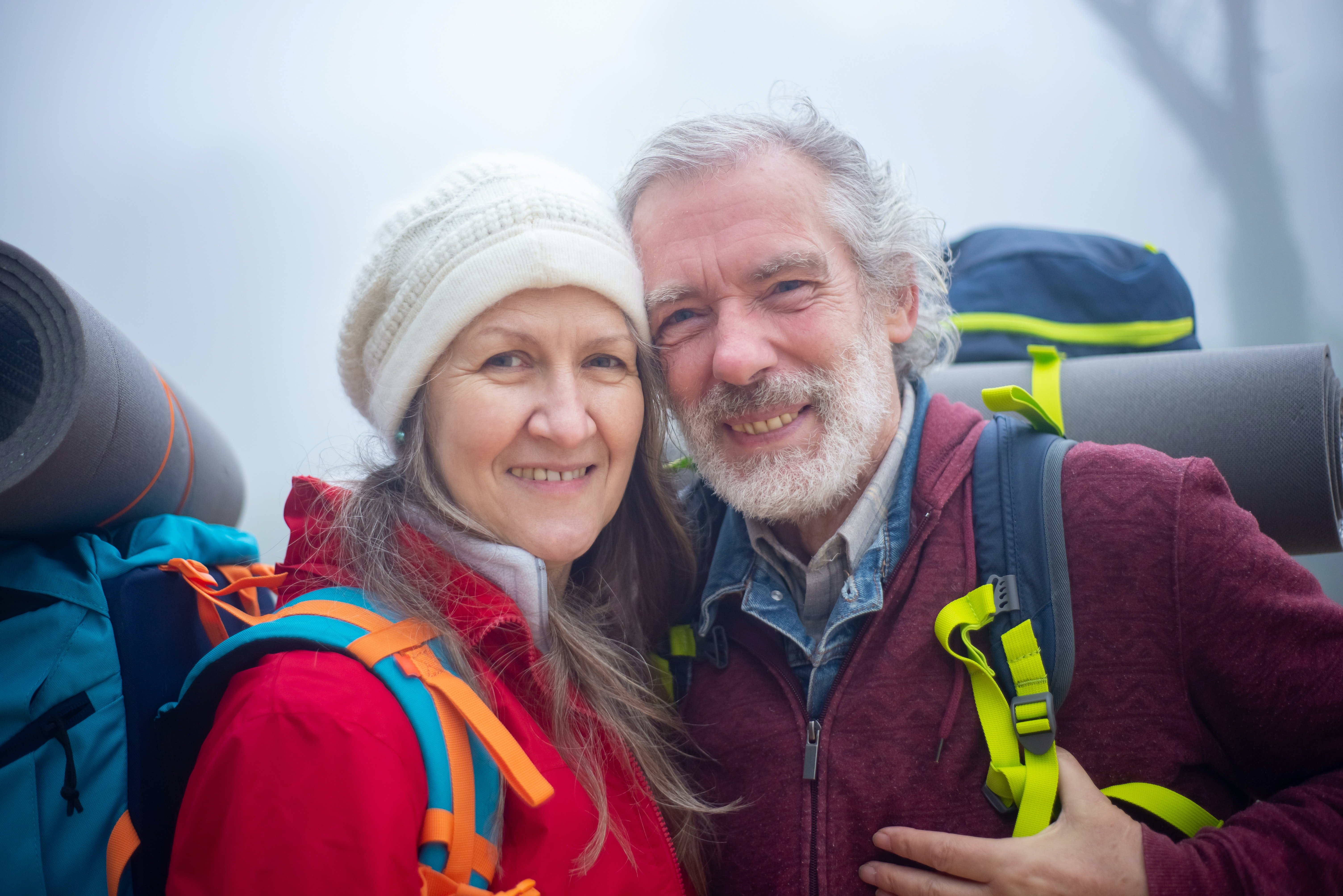 Smiling senior couple on a hike promoting dental care for pensioners
