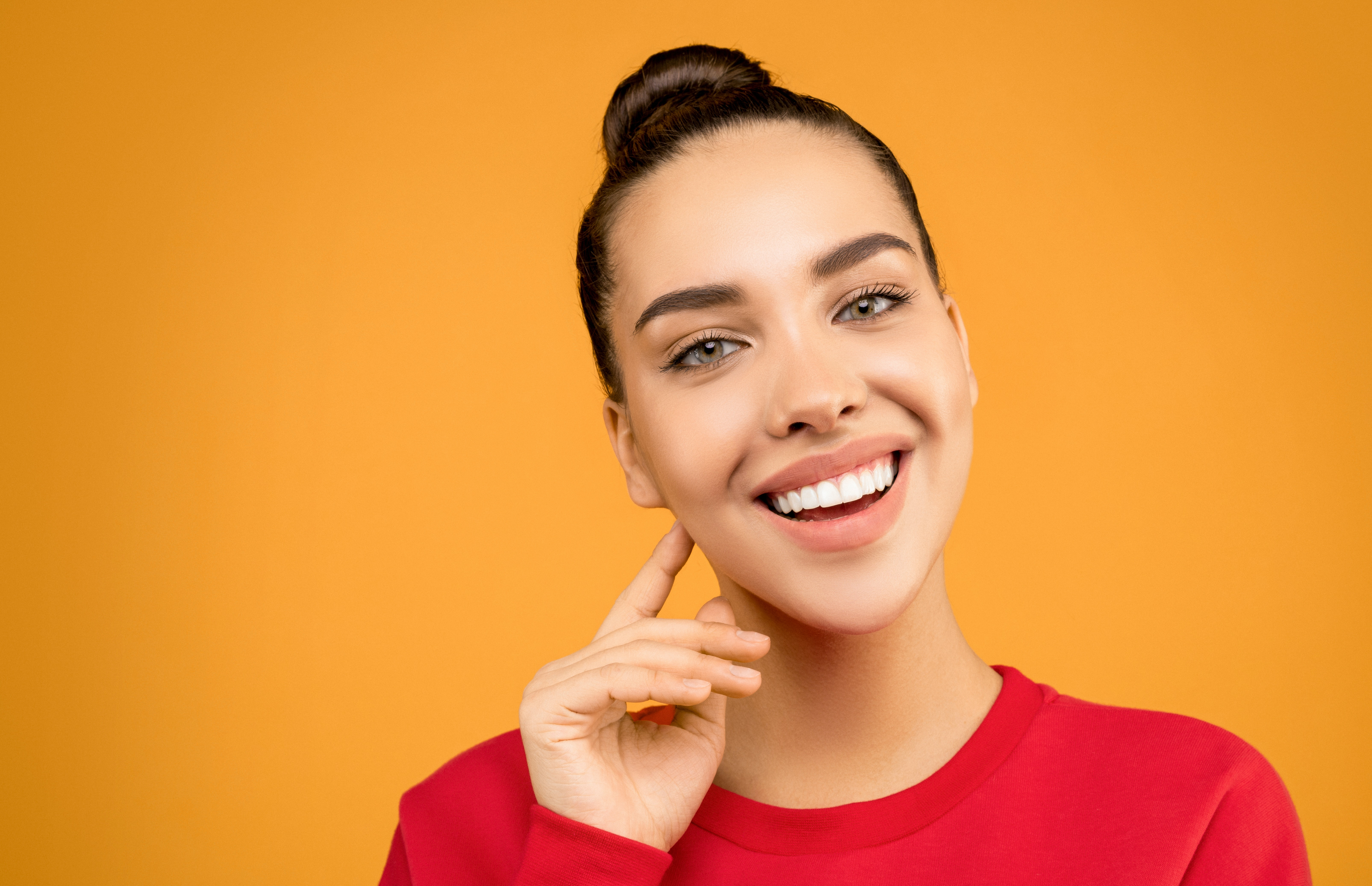 Woman smiling in front of orange background.