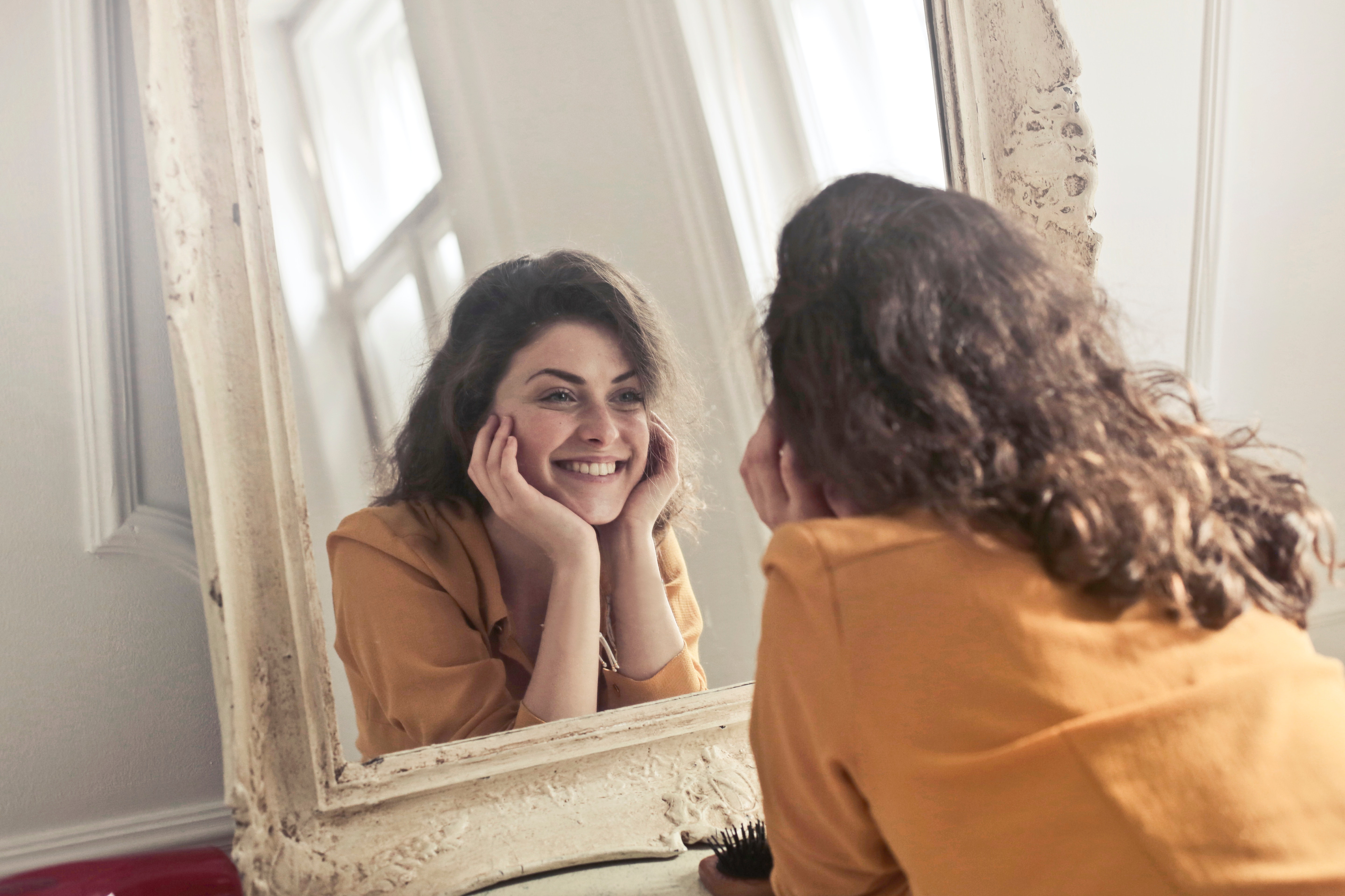 Photo of woman looking in the mirror and smiling
