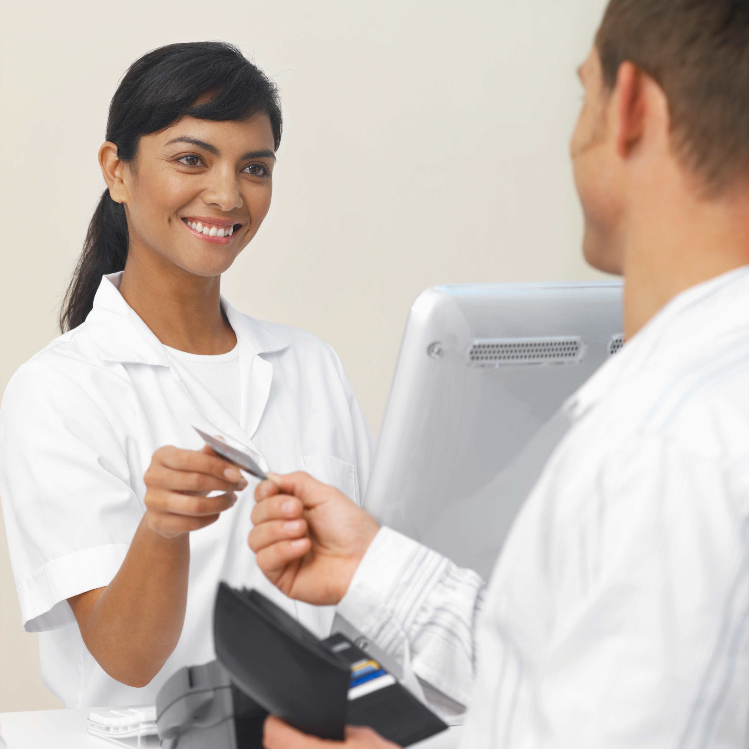 skd242360sdc Close-up of patient paying dental nurse with credit card.jpg