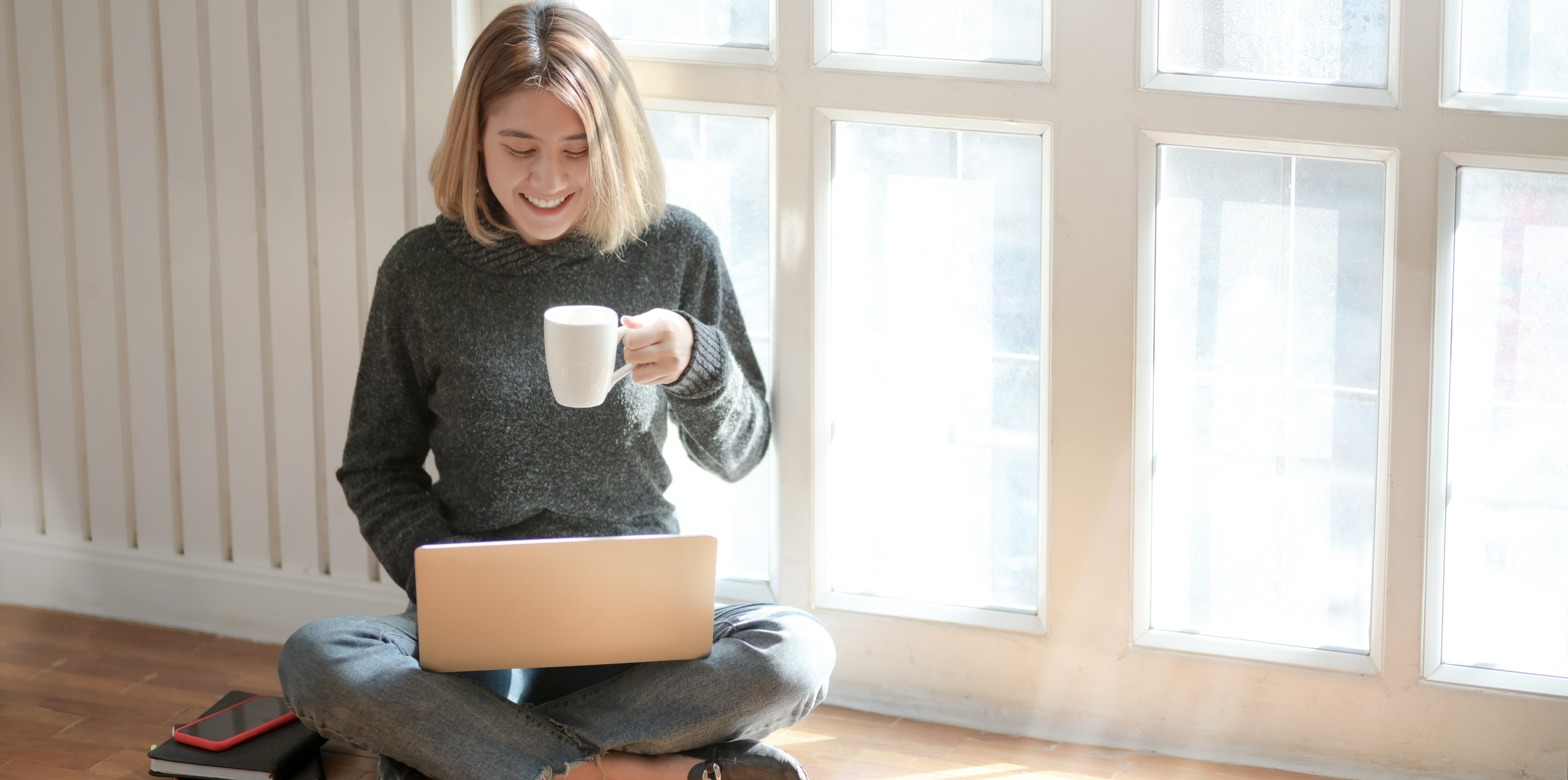 Woman videochatting on laptop holding coffee cup